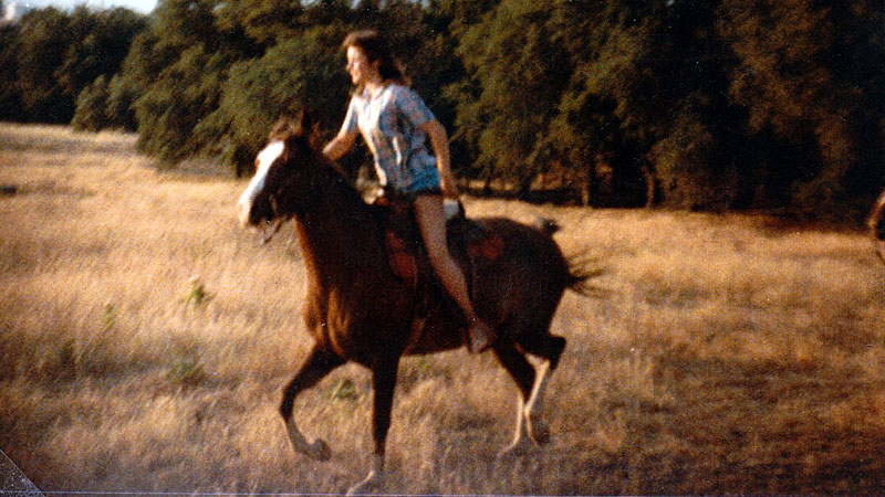 Kim, riding a horse across the California countryside
